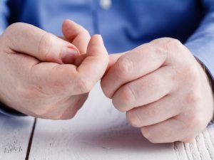 Man picking at fingers nervously