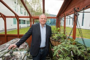 Niall O'Leary poses for a photograph amid plants growing in the greenhouse on the Regeneron site