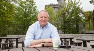 Niall O'Leary sits outside having a coffee at a wooden table, a castle tower visible in the background