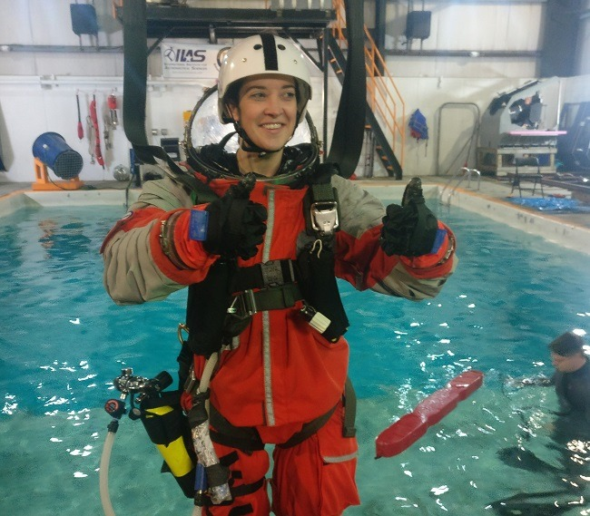 A woman gives two thumbs up while wearing a spacesuit suspended in a harness above a swimming pool.