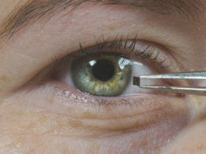 Person holding tiny sensor in front of their eye