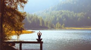 Wellbeing concept depicted by a woman sitting on a jetty in a yoga position facing a breath-taking lake and forest.