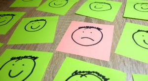Sticky notes depicting one sad face surrounded by happy faces symbolising someone in the wrong company culture.