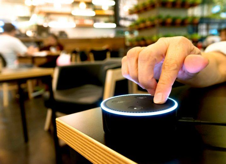 Picture of a hand touching Amazon Echo dot