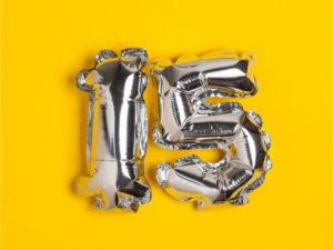 Silver foil number 15 balloons on a golden yellow background
