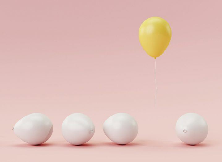 four white balloons on the ground with one yellow one floating - odd one out