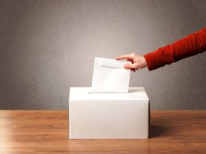 ballot box with someone casting their vote
