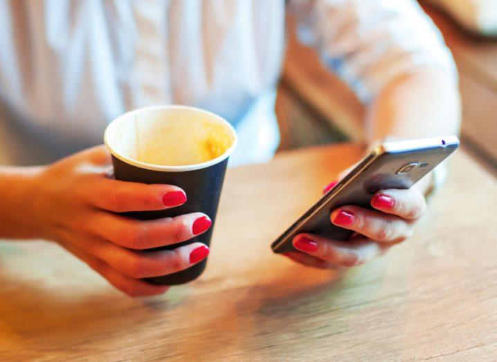 Person using smartphone having coffee