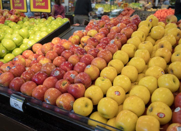 fresh fruit in a supermarket - red apples and oranges