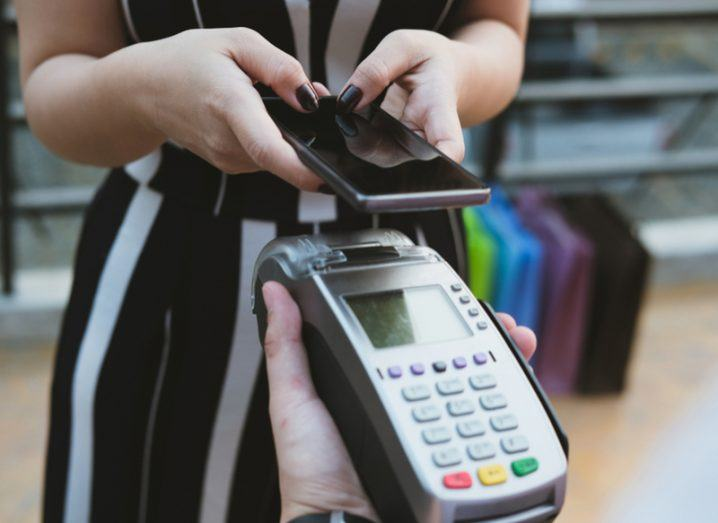 woman making mobile payments on card machine