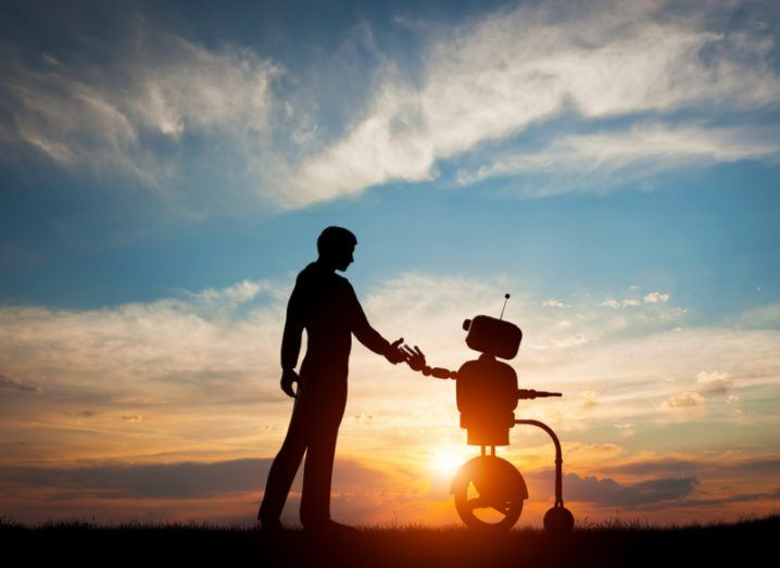 human and robot hold hands against sunset, AI and human concept
