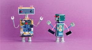 Two little robots on pink background AI artificial intelligence