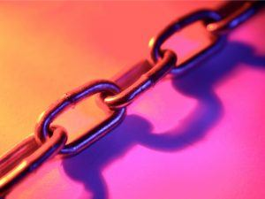 Close-up of links in a steel chain on a brightly coloured background of orange and pink hues