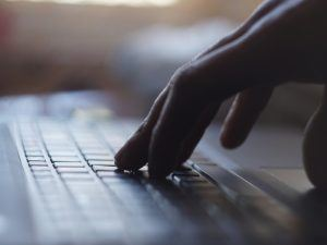 close-up of laptop keyboard with hand resting on it
