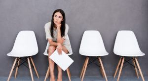 A woman deep in thought about her last job while waiting for an interview while holding her resume.