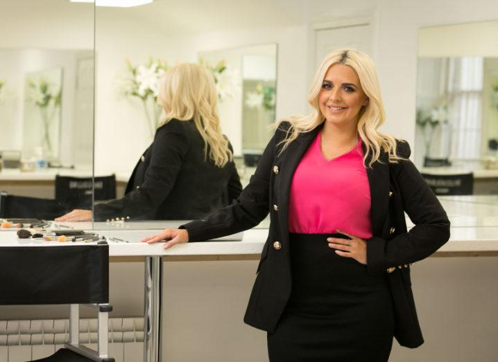 A blonde woman in a black jacket and skirt and fuchsia top stands in front of a mirror reflecting her back. She has one hand on her hip and the other on a shelf next to an array of makeup brushes