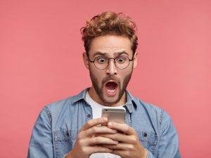Horrified hipster with smartphone