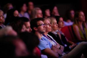 Soft light on an audience in red theatre seats, the focus centres on one man in a blue shirt and glasses