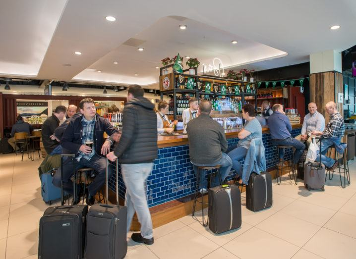 Passengers with wheeled suitcases gather at the Marqette bar in Dublin airport