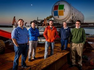 Five men stand at the edge of the dock in Scotland's Orkney Islands in front of a large cylindrical white vessel bearing the Microsoft logo, ready to be deployed on the sea floor