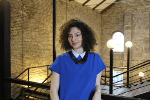 A woman with short, dark curly hair in a royal blue shirt dress poses by a rail overlooking a spacious stairway surrounded by brickwork walls