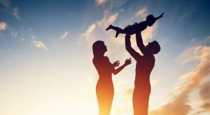 Silhouette of parents on parental leave holding their child happily in the air against a sunset