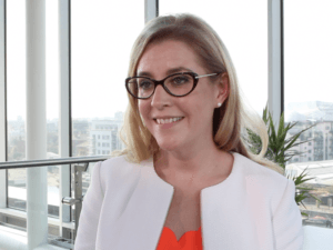 A blonde woman wearing glasses, a white blazer and bright orange blouse stands in front of a window overlooking Dublin's docklands