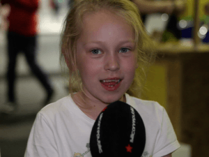 Close-up of a young girl in a white T-shirt being interviewed with a Silicon Republic microphone in front of her face