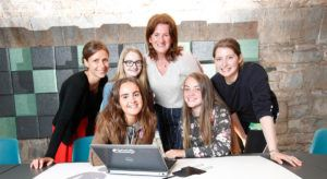teen-turn students and mentors smiling in front of laptop