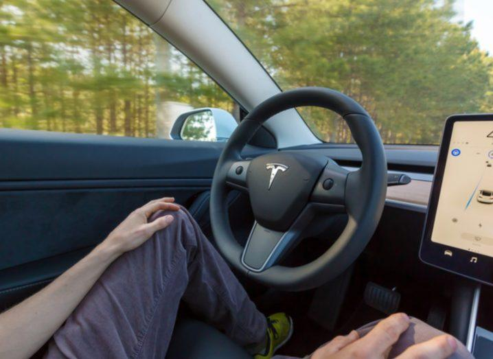 Person driving Tesla Model 3 in autopilot mode
