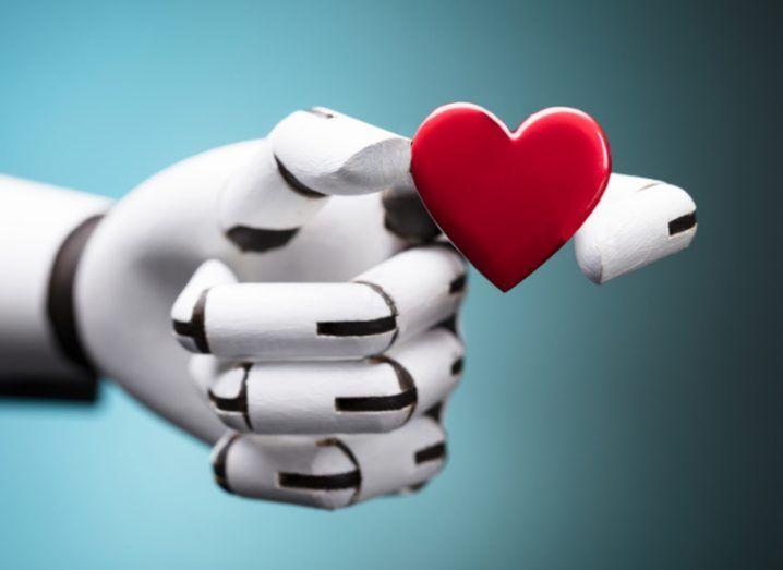 robot hand holding a heart