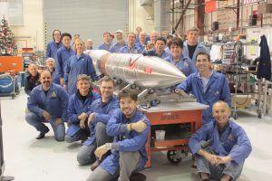 team in blue overalls gathered around rocket