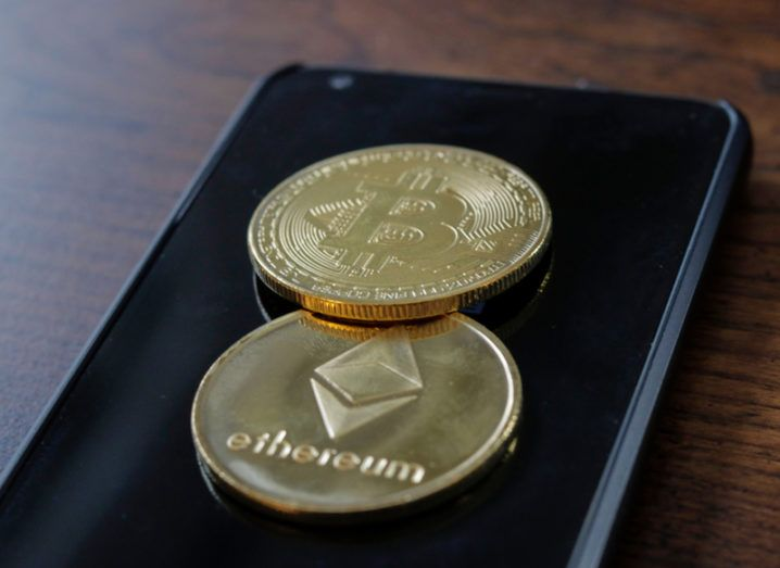 3D representation of a bitcoin and an ether coin on top of a smartphone