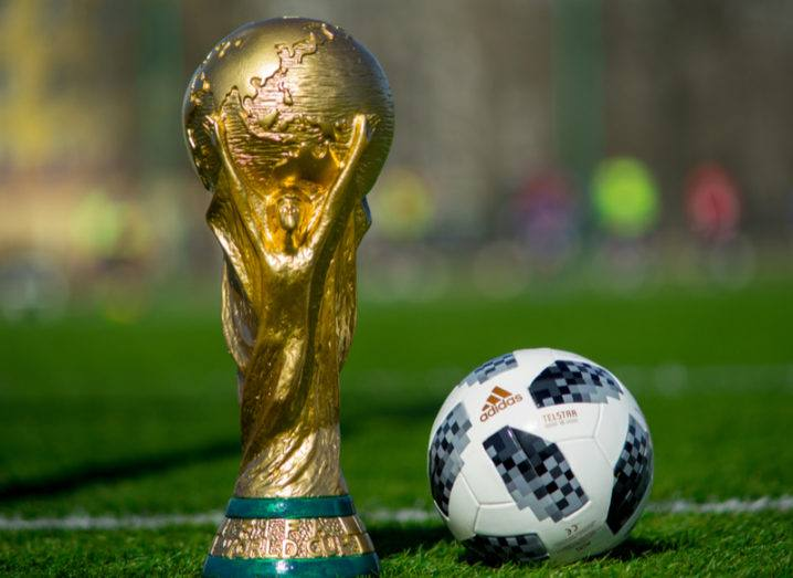 Trophy of the FIFA World Cup and official Adidas Telstar 18 ball on a football pitch.