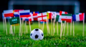 A soccer ball sitting on the grass in front of various miniature flags depicting the World Cup