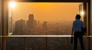 Young business man looking out window at sunrise in metropolitan area. Looking ahead at trends.