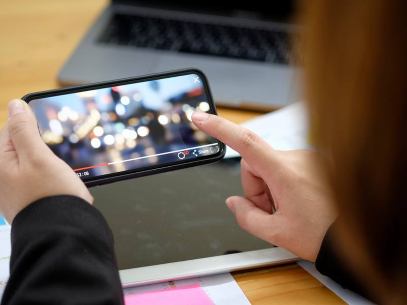 close-up of hands holding a mobile playing a video - 5G