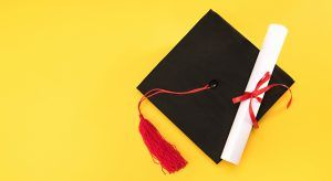 Graduation cap and scroll against yellow background. Results of Udemy survey into the most in-demand skills for 2018.