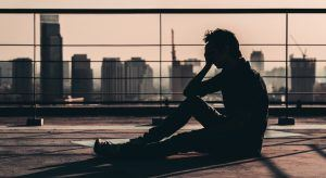 silhouette of man suffering mental health issues sitting on a rooftop overlooking a metropolitan skyline