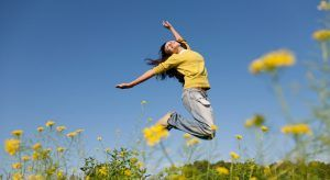 Woman jumping for joy in a ragweed-dotted field on a clear sunny day because of all the jobs that were created in Ireland this week