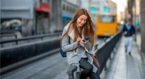 Woman sitting on a rail in a city, smiling and texting her friends to stay in touch.