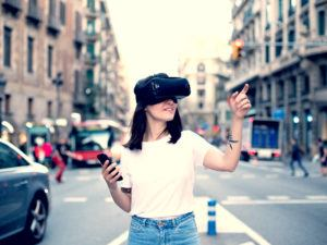 developer wears virtual reality googles in a modern urban city controls it with smartphone