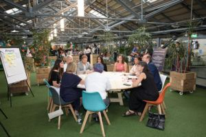 Participants seated at a round table with Prince Harry and Meghan Markle in an open space in Dogpatch Labs at the CHQ building