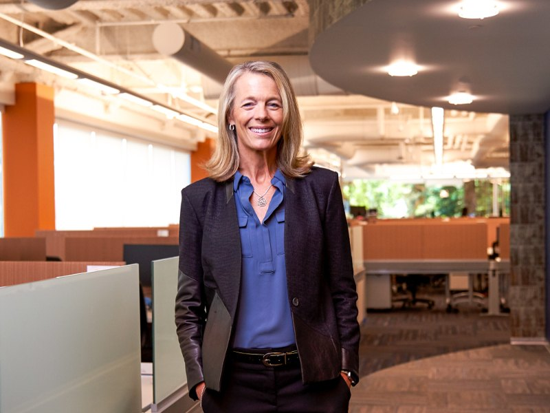 Diana McKenzie in a shirt, blazer and trousers, smiles in an empty Workday office.