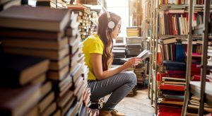 Young woman sitting in a library reading with headphones on surrounded by books trying to reskill for her career.