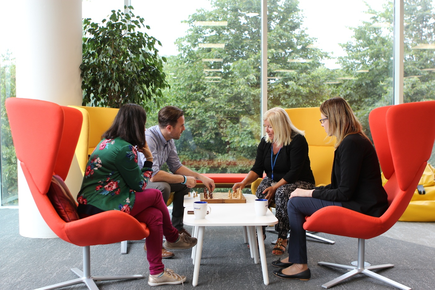 Four Globoforce employees sitting in colourful chairs playing chess