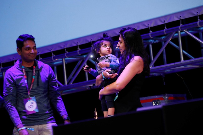 Surbhi Sarna stands on the Inspirefest stage holding her young child in her arms as her husband, Rajeev, looks on and smiles