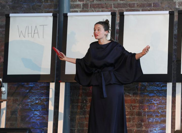 Ada's Army creator Zoe Philpott stands on stage in front of three flipcharts in front of a brick wall, one chart simple reads: 'WHAT'