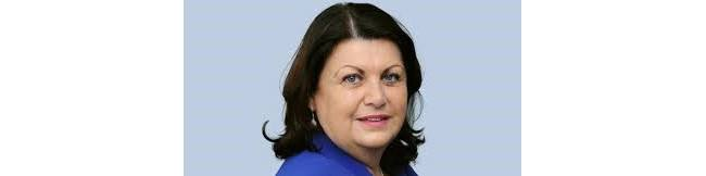 Máire Geoghegan-Quinn's headshot against a sky blue background
