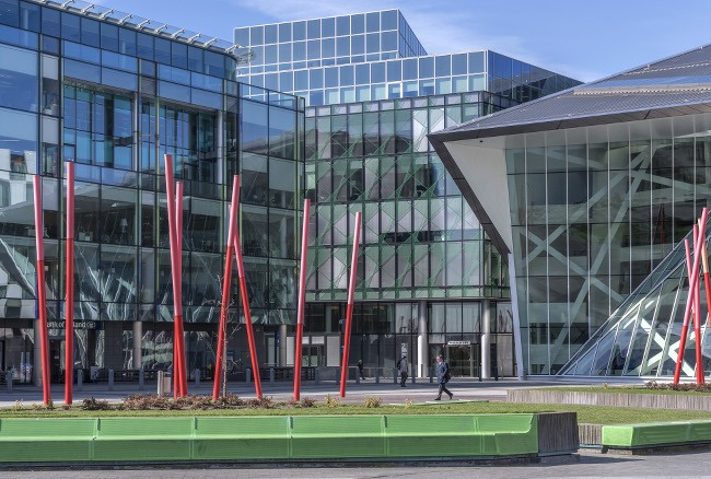 Grand Canal Square on a sunny day, glass buildings visible in the background, and green spaces and striking red sculpture in the foreground
